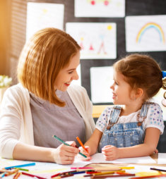 smiling mother teaching her daughter to color