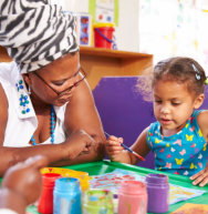 african mother teahing to her daughter to paint